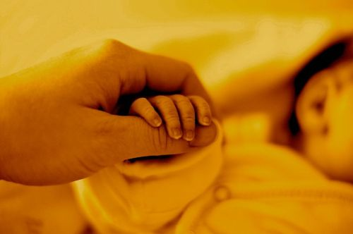 Newborn holding mothers thumb. A little grain, shot at 250 ISO